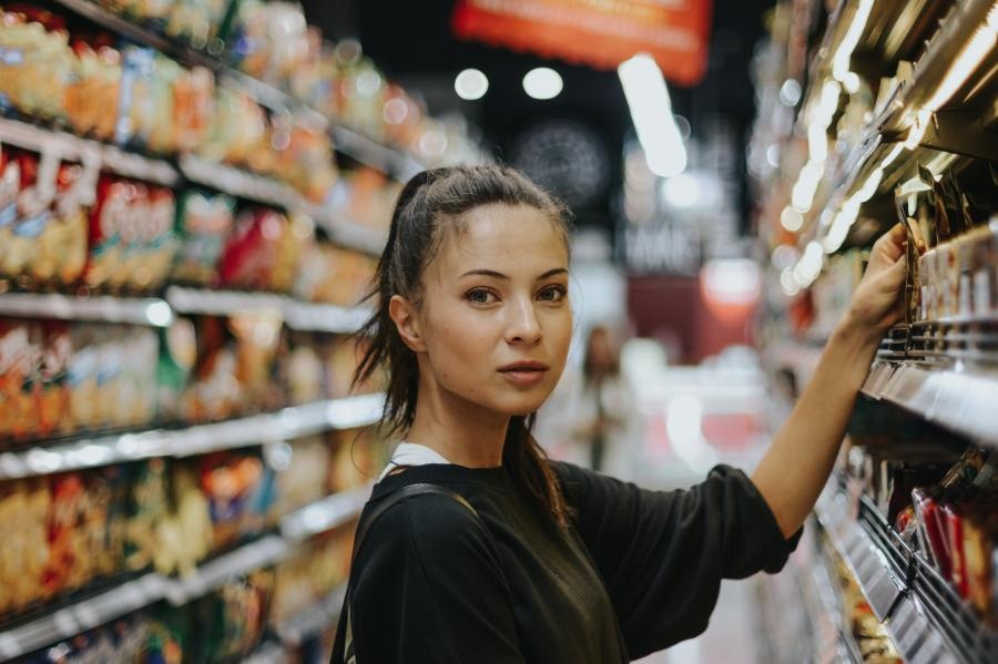 Decorative photo of a young woman selecting products in a supermarket.